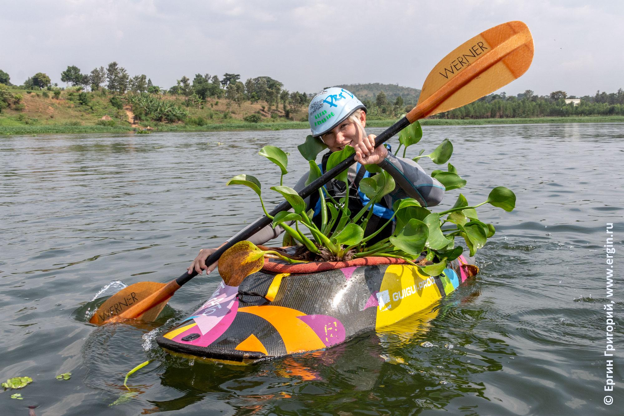 Каякер в окружении водорослей на каяке с веслом