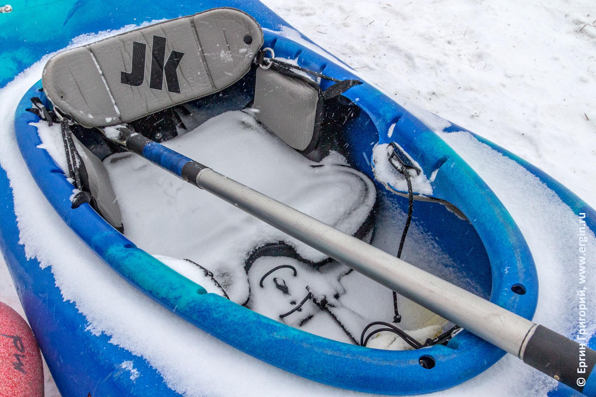Каяк засыпан снегом и весло в очке