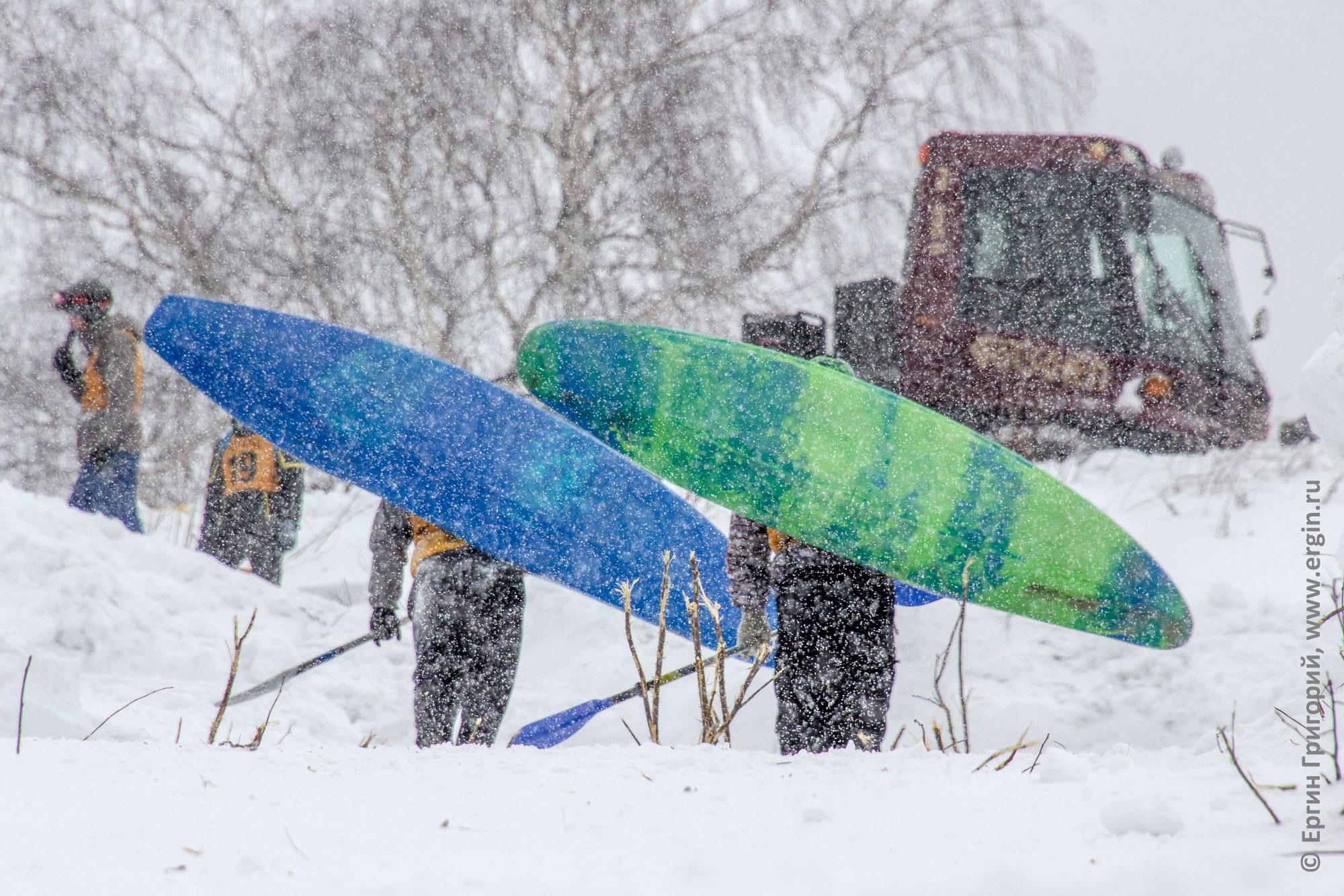 Сноукаякеры несут каяки под идущим снегом