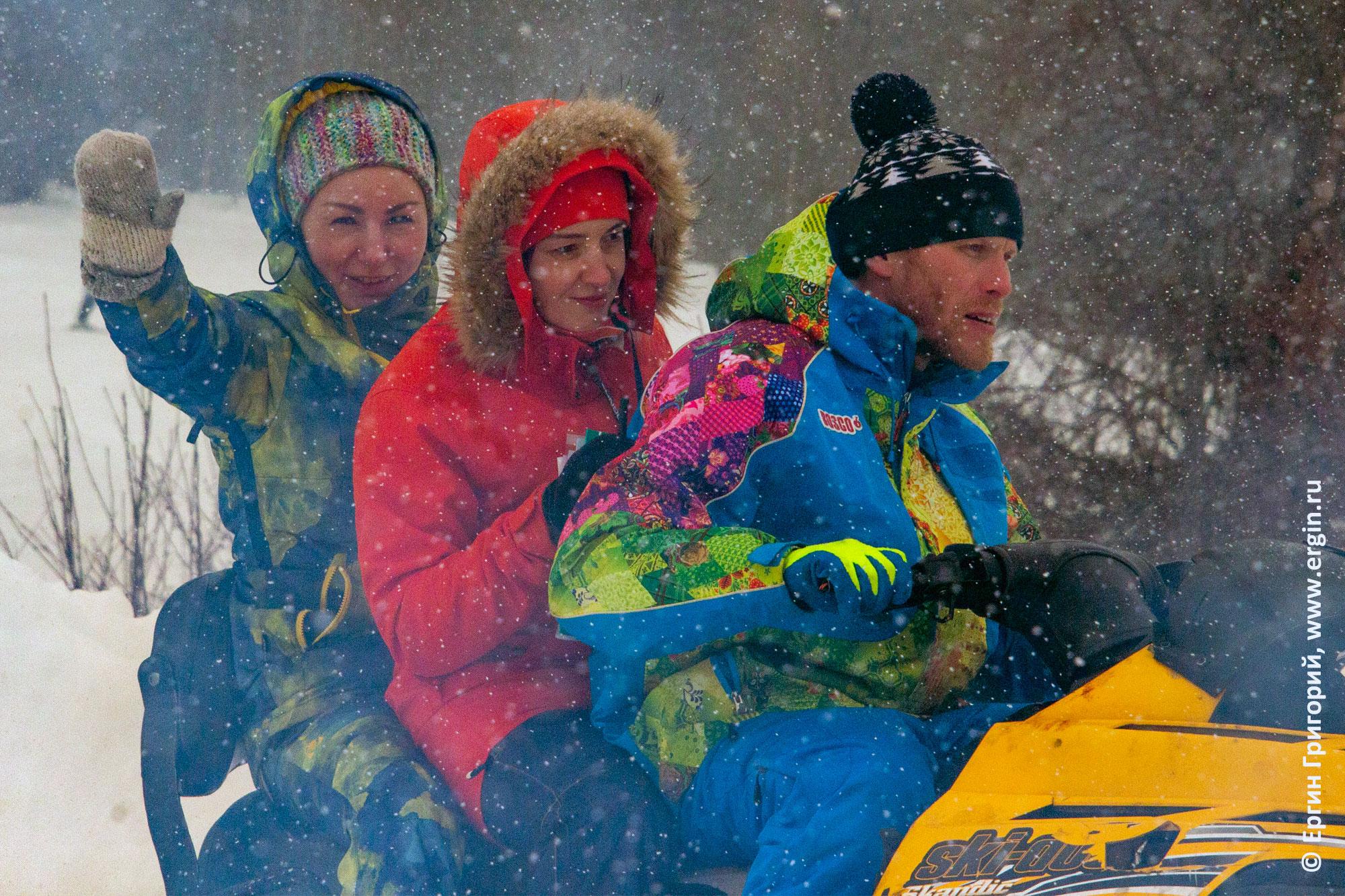 Девушки едут на снегоходе