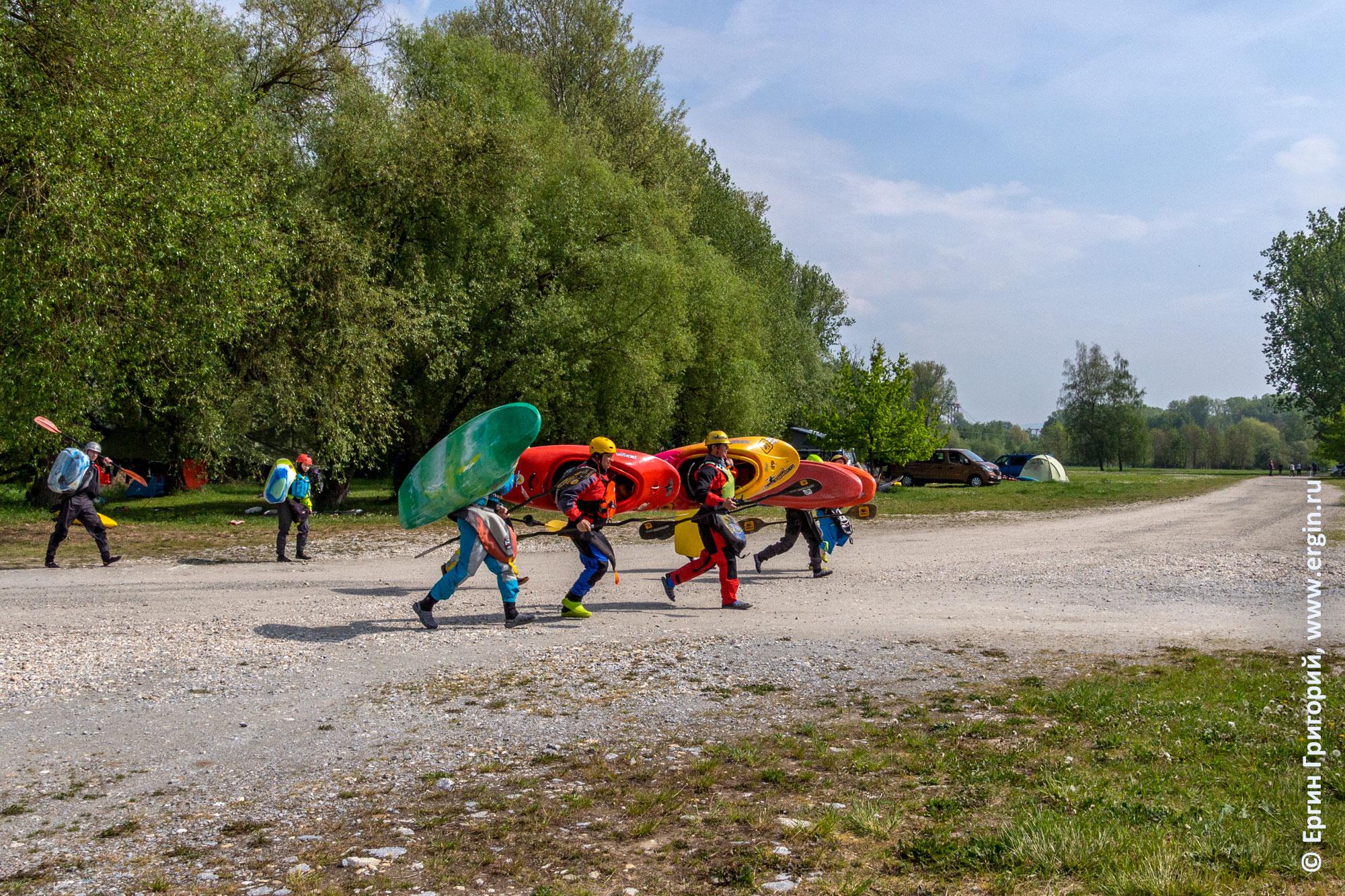 Каякеры с каяками идут на тренировку по фристайлу на бурной воде