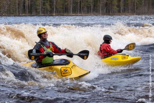 Каякеры серфят вместе на валу фристайл-каякинг на бурной воде