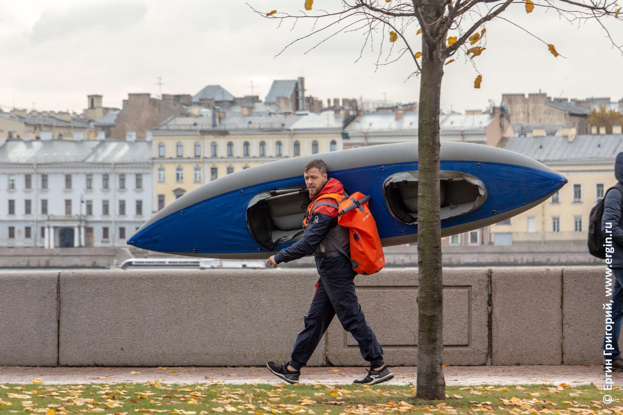 Байдарочник с байдаркой идет по набережной Невы в СПб