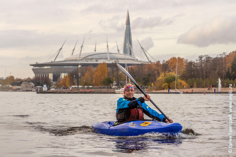Каякер идет по Малой Невке на фоне стадиона Газпром Арена и башни Газпрома
