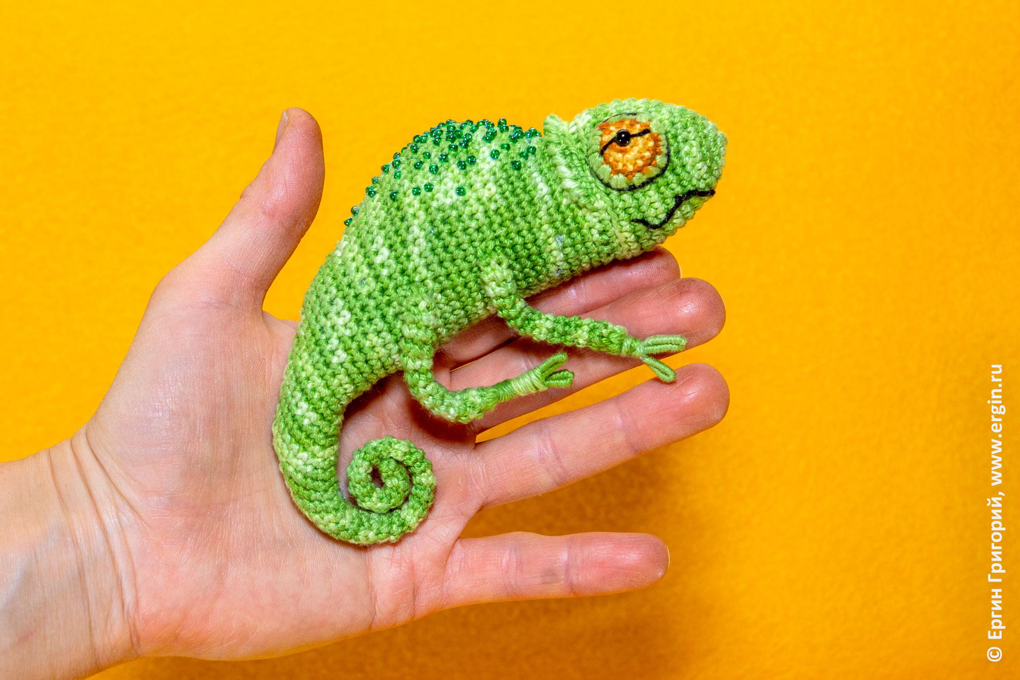 Рукодельный хамелеон сидит на руке