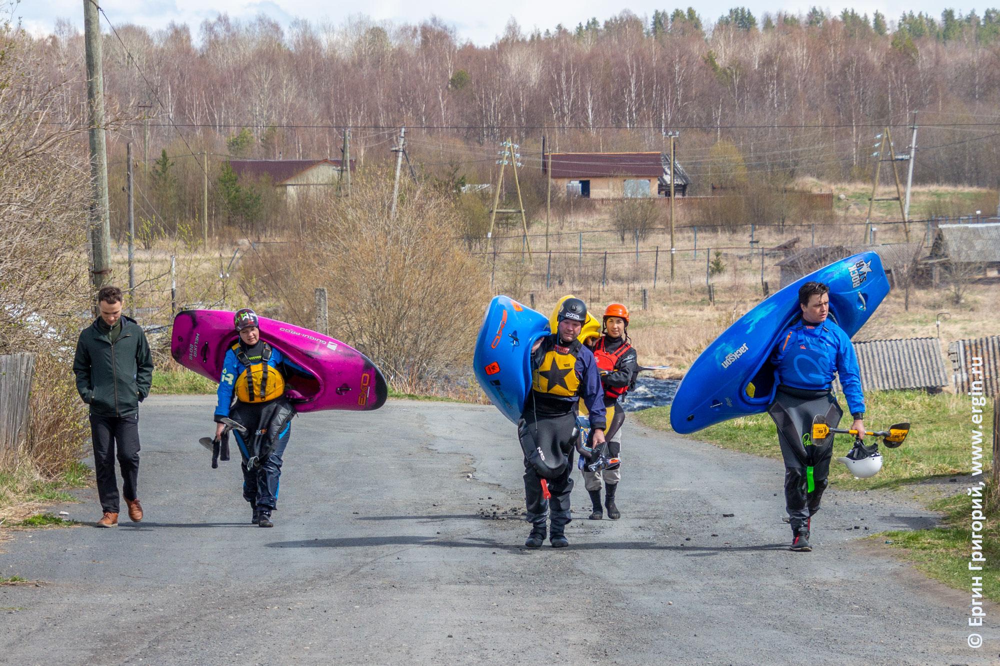 Каякеры идут домой с каяками после тренировки