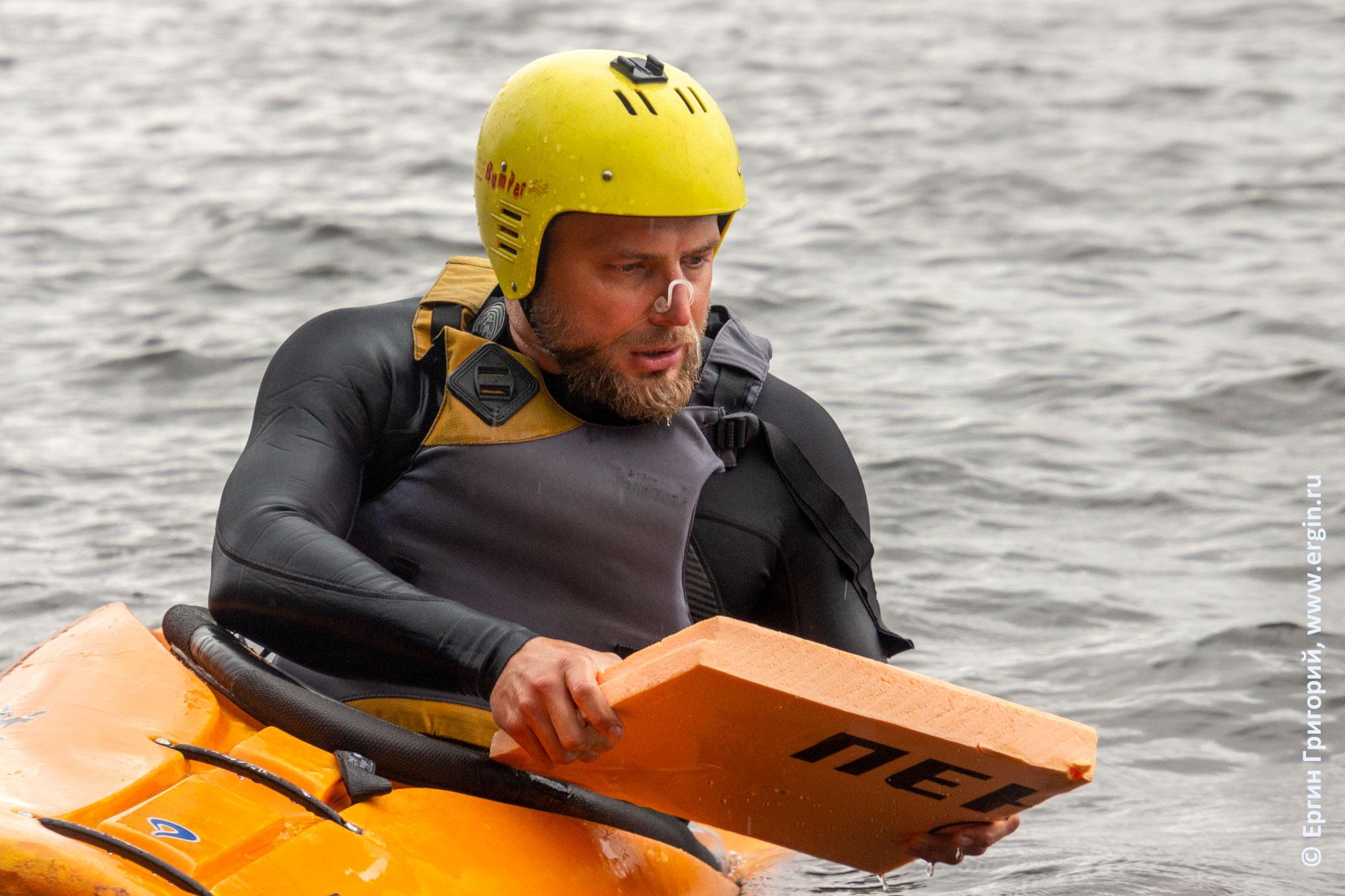 Новичок-каякер встает на каяке с досочкой для плавания
