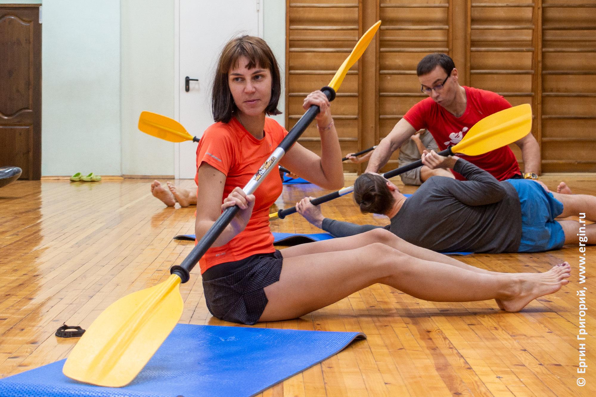 Девушка с веслом на тренировке по каякингу