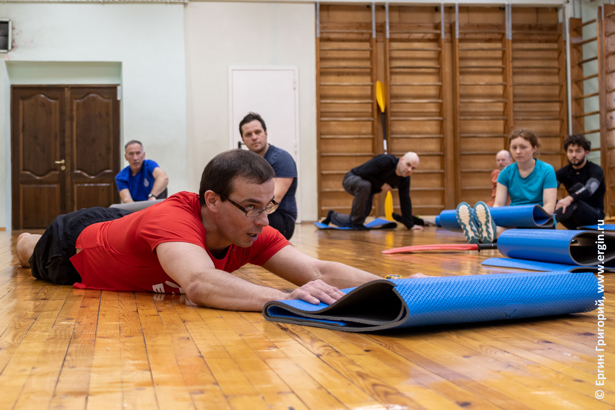 Инструктор показывает упражнения на суше для изучения вставания на каяке