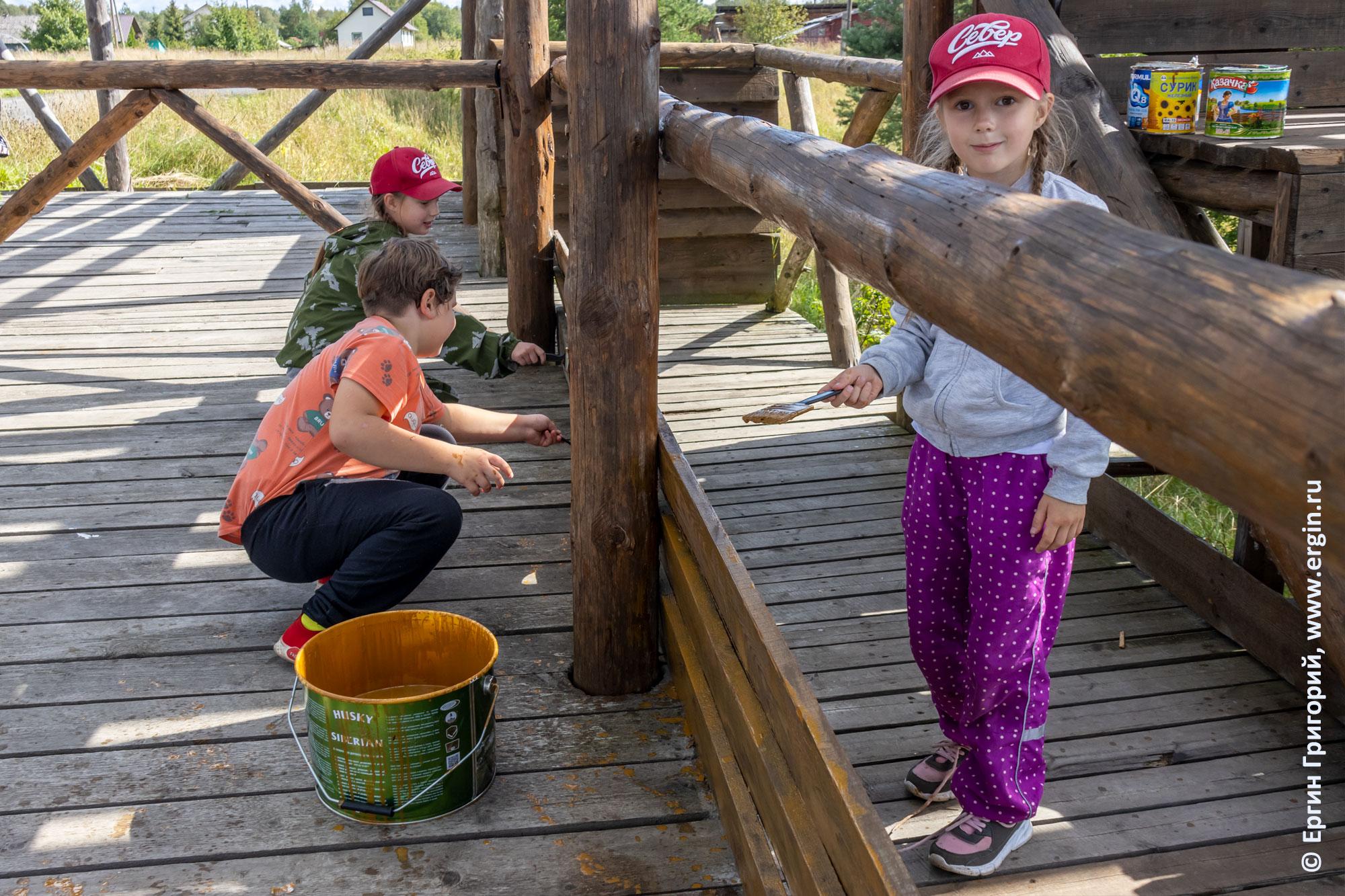 Дети помогают наносить пропитку на доски трибуны и судейской в Тивдии