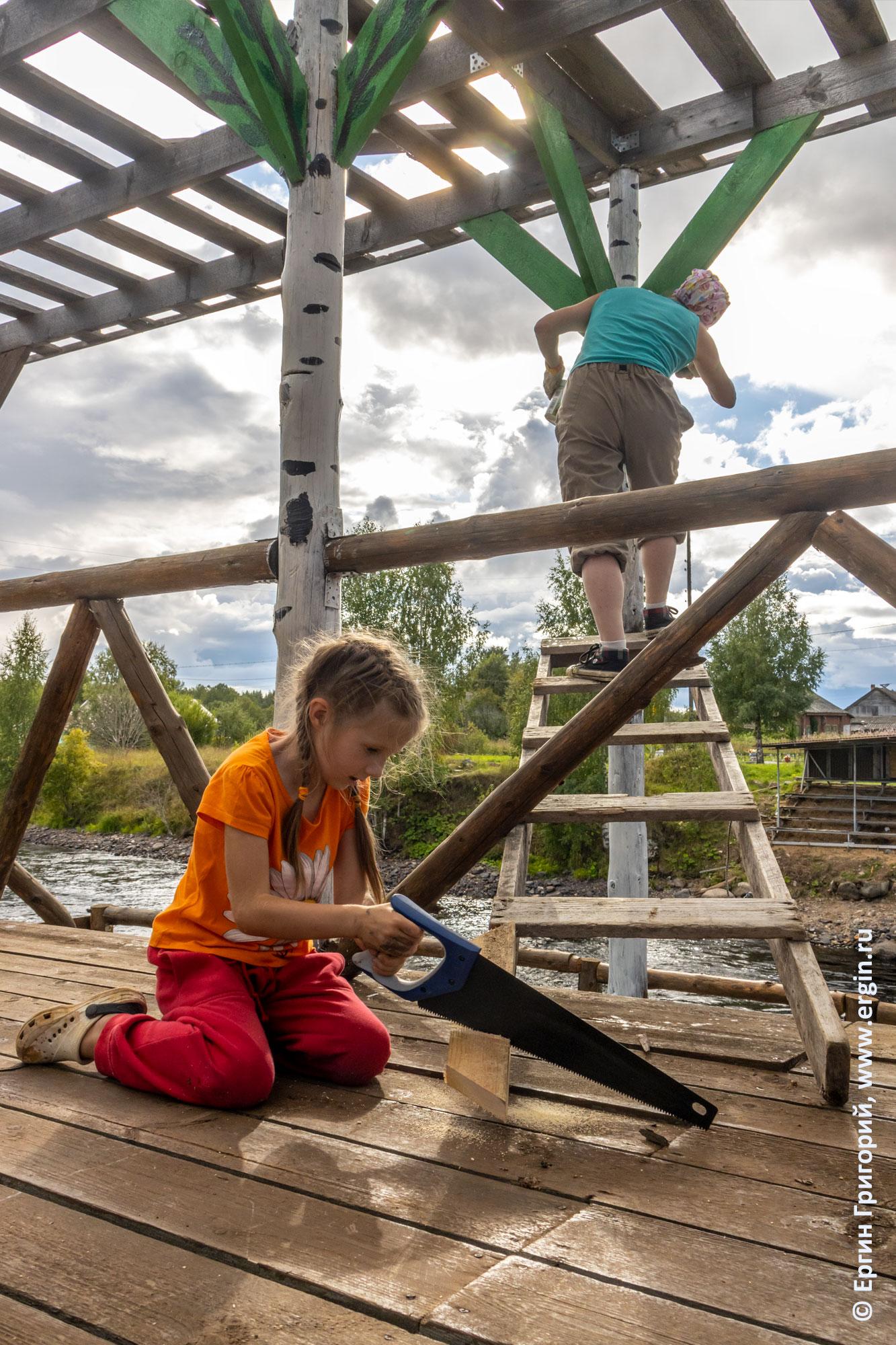 Девочка с пилой помогает ремонтировать постройки для соревнований в Тивдии