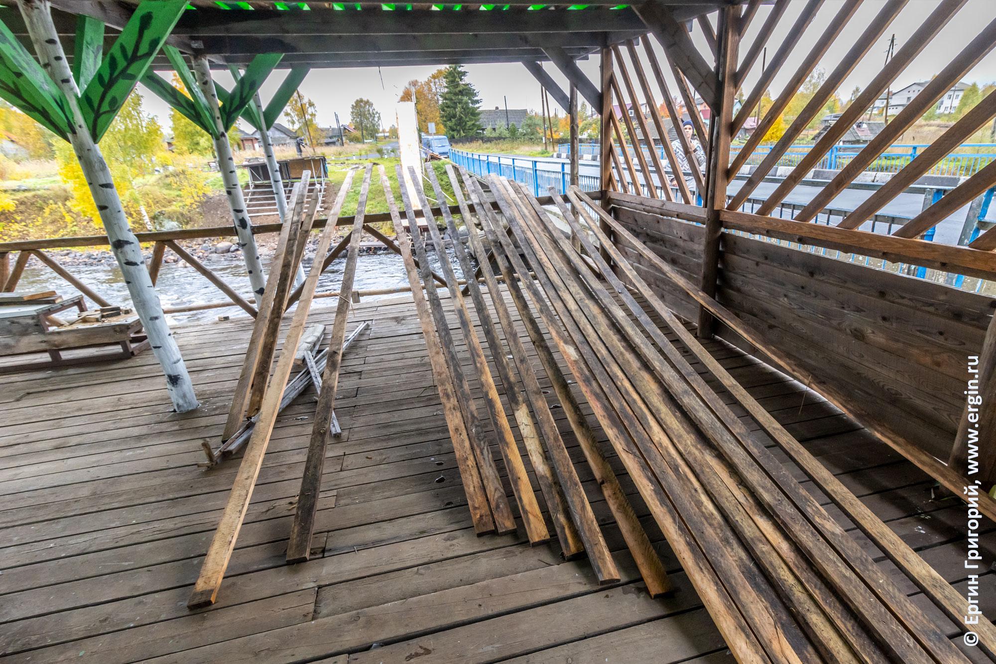 Доски для скамеек сушатся под крышей
